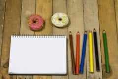 Smakliga och nya donuts och en anteckningsbok, blyertspennor för att dra Sket Royaltyfri Foto