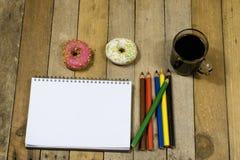 Smakliga och nya donuts och en anteckningsbok, blyertspennor för att dra Sket Royaltyfria Bilder