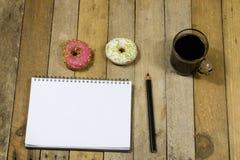 Smakliga och nya donuts och en anteckningsbok, blyertspennor för att dra Sket Arkivbild
