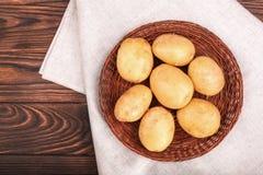 Smakliga och nya potatisar på en trätabell för mörk brunt Näringsrika organiska potatisar på ett ljust tyg Rå och nya grönsaker Arkivbilder