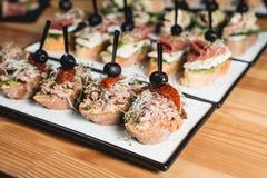 Smakliga pinchos med tonfisk, torkad tomat-, oliv- och pestosås, traditionellt spanskt mellanmål som tjänas som på en vit platta royaltyfri bild