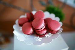 Smakliga söta hemlagade makaronikakor, vit snör åt maträtten med rosa sötsaker royaltyfri fotografi