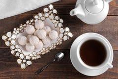 Smakliga söta kokosnötgodisar i en vas med te på en brun trätabell ovanför sikt royaltyfri bild