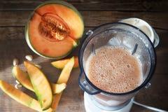 Smakliga Smoothies av cantaloupmelon-melon i hel och skivad mogen organisk cantaloupmelon-melone en blandare, på träbakgrund, lan fotografering för bildbyråer