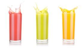 Smakliga sommarfruktdrinkar i exponeringsglas med färgstänk Arkivfoto