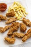 Smakliga stekt kycklingtrumpinnar, kryddiga vingar, pommes frites och fega fingrar med sur-sötsak sås på bakplåten över vit att u royaltyfria bilder
