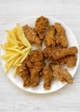 Smakliga stekt kycklingtrumpinnar, kryddiga vingar, pommes frites och fega fingrar p? den vita plattan ?ver vit tr?yttersida, b?s arkivfoto