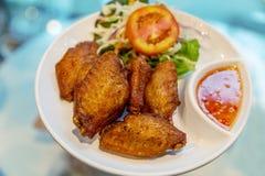 Smakliga stekte frasiga fega vingar och tomatgrönsak med sås Maträtt för matställe på den vita plattan royaltyfri foto