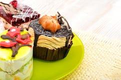 Smakliga tarts, kakor med kräm på den gröna plattan Royaltyfri Bild