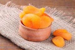 Smakliga torkade aprikors i en träbunkecloseup på en brun bakgrund Arkivfoto