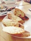 Smakligt bröd med vitlök, ost och örter i den vita maträtten på tabellen Royaltyfria Bilder