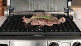 Smakligt kött släntrar av nötkött på elektriskt galler arkivfilmer