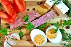 Smakligt mellanmål med tomaten, gelé, vitlök, feta, det kokta ägget och gräsplaner royaltyfri bild