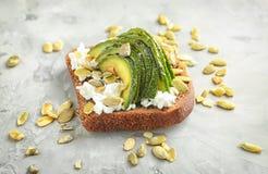Smakligt rostat bröd med avokadot på grå bakgrund royaltyfri fotografi