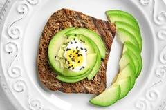 Smakligt rostat bröd med avokadot på plattan, closeup arkivfoto