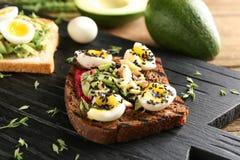 Smakligt rostat bröd med avokadot på träbräde royaltyfri fotografi