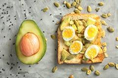 Smakligt rostat bröd och avokado på grå bakgrund, bästa sikt royaltyfri bild
