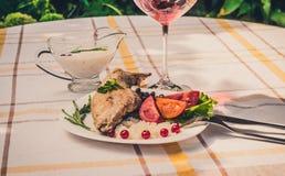 Smakosz piec królik nogę z ryż i fasolami Biały kumberland i szkło czerwone wino Posiłek słuzyć na bielu checke i talerzu po pros Obraz Royalty Free