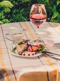 Smakosz piec królik nogę z ryż i fasolami Biały kumberland i szkło czerwone wino Posiłek słuzyć na bielu checke i talerzu po pros Obrazy Stock