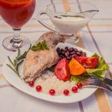 Smakosz piec królik nogę z ryż i fasolami Biały kumberland i szkło pomidorowy sok Posiłek słuzyć na bielu talerzu i ch po prostu Fotografia Stock