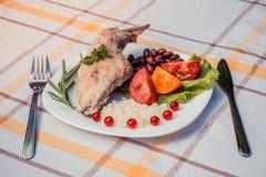 Smakosz piec królik nogę z ryż i fasolami, biały kumberland Posiłek słuzyć na bielu talerzu i sprawdzać stołowym płótnie z cu po  Zdjęcia Royalty Free