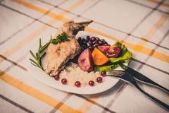 Smakosz piec królik nogę z ryż i fasolami, biały kumberland Posiłek słuzyć na bielu talerzu i sprawdzać stołowym płótnie z cu po  Fotografia Stock