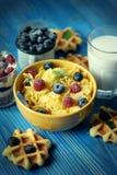 Smakowici cornflakes z malinkami i czarnymi jagodami na błękitnym tle Opłatki i mleko zdjęcia royalty free