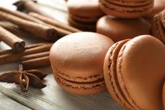 Smakowici czekoladowi macarons i cynamon na drewnianym tle obraz stock
