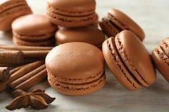 Smakowici czekoladowi macarons i cynamon na drewnianym tle obrazy stock