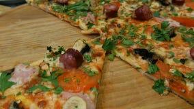 Smakowita świeża rżnięta pizza z Bawarskimi kiełbasami, pieczarki, bekon, pomidory, zielenieje Zamknięty widok zdjęcie wideo