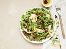 Smakowita jarska sałatka z karczochem, rakietą, suszącymi pomidorami i oliwkami, Fotografia Stock