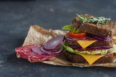 Smakowita kanapka robić chleb, pomidory, kiełbasa, cebula i sałata, na ciemnym tle, selekcyjna ostrość Fotografia Stock