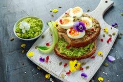 Smakowita kanapka z avocado gotował się jajka, dyniowego ziarna i jadalnych altówka kwiatów w białej desce, zdrowa żywność Obrazy Stock