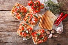 Smakowita kanapka z białymi fasolami, pomidorami, serem i ziele clos, Zdjęcia Stock
