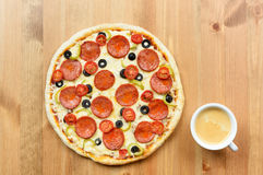 Smakowita, przyprawiona pizza, i białej filiżanki kawowa kawa espresso na drewnianym tle Zdjęcia Royalty Free