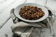 Smakowita wanilia i czekoladowi kukurydzani płatki w białym talerzu na białym drewnianym tle obok metal łyżki na popielatym, Zdjęcia Royalty Free