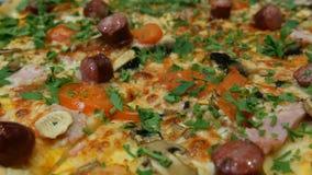 Smakowita ?wie?a pizza z Bawarskimi kie?basami, pieczarki, bekon, pomidory, zielenieje Zamkni?ty widok zdjęcie wideo