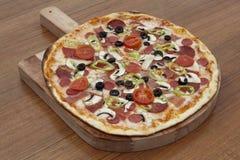 Smakowita wyśmienicie pizza z salami na starych deskach Obrazy Royalty Free