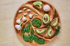 Smakowite avocado grzanki na drewnianym talerzu z solą, świeżym czosnkiem, basilów liśćmi i koperem, Jarskie avocado kanapki Obraz Stock