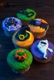 Smakowite Halloweenowe babeczki ustawiać z kolorowymi dekoracjami robić c zdjęcia stock