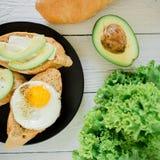 Smakowite kanapki z avocado i jajkiem na czarnym talerzu na drewnianym stole Wyśmienicie naturalny śniadanie zdjęcie royalty free