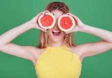 Smakowite tropikalne owoc! Atrakcyjna plciowa kobieta trzyma świeżą soczystą grapefruitową lub pomarańczową pobliską twarz z pięk Zdjęcie Stock