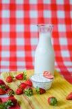 Smakowity śniadanie, świeży mleko w szklanej butelce, smakowity jogurt w małym szklanym pucharze z mnóstwo truskawkami wokoło obraz royalty free