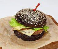 Smakowity czarny hamburger kropiący z sezamowymi ziarnami z kurczakiem, sałatką, serem i kumberlandem, obrazy stock
