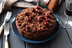 Smakowity domowej roboty czekoladowy tort z czekoladowym lodowaceniem i surowymi wiśniami słuzyć z czerwonym winem na ciemnym tle obrazy stock