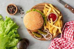 Smakowity hamburger i Francuscy dłoniaki Na Drewnianej porci desce zdjęcie stock