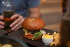 Smakowity hamburger z francuzów dłoniakami słuzyć na stole obrazy royalty free