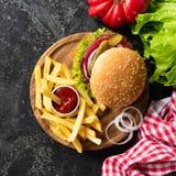 Smakowity hamburger z wołowiną, francuzów dłoniakami i ketchupem na ciemnym tle, fotografia royalty free