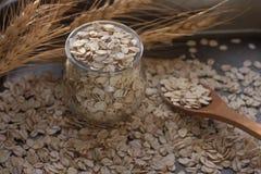 Smakowity odżywczy oatmeal, szklany słój, drewniana łyżka i ucho kukurudza na ciemnym tle, selekcyjna ostrość Obraz Royalty Free