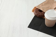 Smakowity pączek w papierowej torbie i kawie na drewnianym stole zdjęcia royalty free